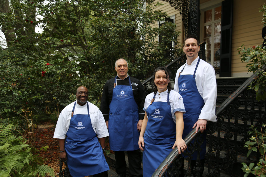 The four 2020 Chef Ambassadors stand on a set of stairs in front of greenery. From left to right, the chefs are Chef Kevin Mitchell, Chef Raffaele Dall'erta, Chef Jamie Daskalis, and Chef Jason Tufts.